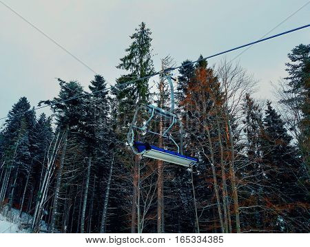 Cableway between the forest trees on a cold winter day at ski resort.
