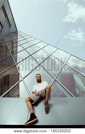Bearded Tattooed Hipster In Front Of Office Building