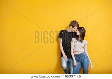 Inlove Couple Posing In Fashion Style On Yellow Wall
