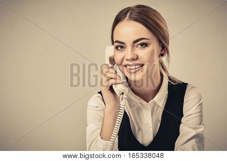 portrait of young secretary answering telephone. Young woman in classical shirt sitting at a desk with a telephone.