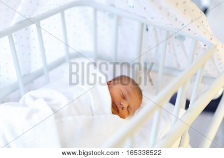 Cute adorable baby girl. sleeping in white birth hospital bed. Newborn child three days old laying in bed. Family, new life, childhood, beginning concept.