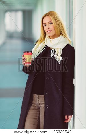 blond woman holding coffee to go in hall.