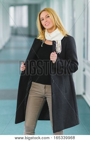 Blond fashion woman dressed coat stand in lobby.