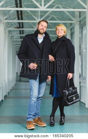 Elegant couple dressed in coat standing at lobby.