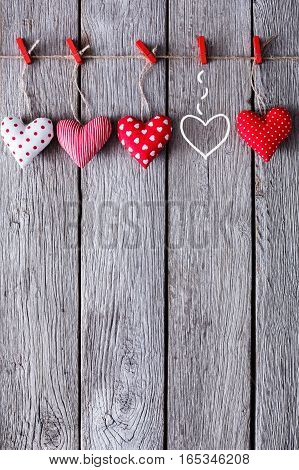 Valentine background with diy handmade sewed pillow hearts on red clothespins at rustic blue wood planks. Happy lovers day card mockup, copy space, vertical