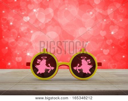 Cupid icon with eyeglasses toy on wooden table over blur red background Valentines day concept