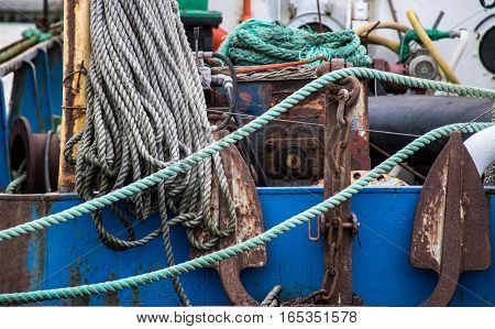 Small fishing boat close up with part of the anchor