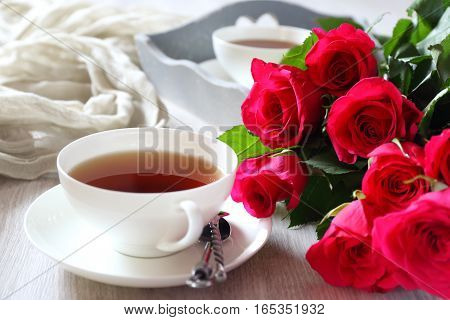 Valentine's Day: Romantic morning Tea Party for two with burning candles and bouquet of red roses
