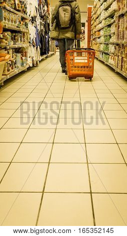 Man walking in a supermarket hall with a red basket