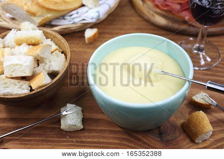Traditional cheese fondue with baguette and glass of red wine