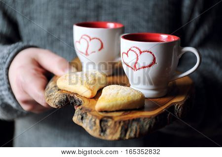 Valentine's Day: two cups of coffee in the men's hands and heart cookies on a wooden tray. Focus selective