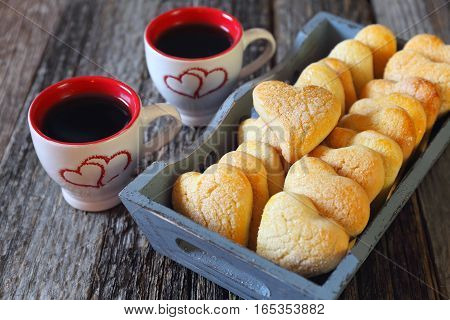 Valentine's Day: two cups of coffee and heart cookies in wooden tray