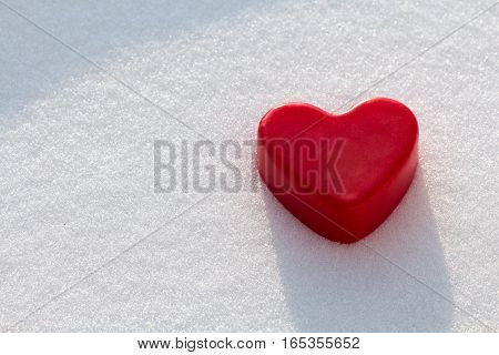 Lonely red wax heart out in the snow