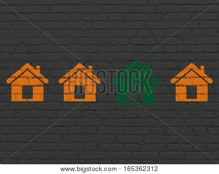 Protection concept: row of Painted orange home icons around green home icon on Black Brick wall background