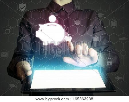 Image of a girl with a tablet in hands. She touches money box icon. Concept accumulation storage of funds internet for banking finance trading.
