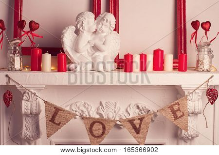Two marble angels in love near many white and red candles and valentines decor