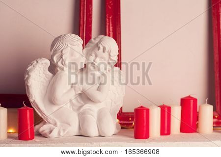 Two marble angels in love near many white and red candles; valentines decor