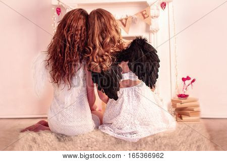 Backs of two girls with white and black wings sitting near the valentines decorations in studio