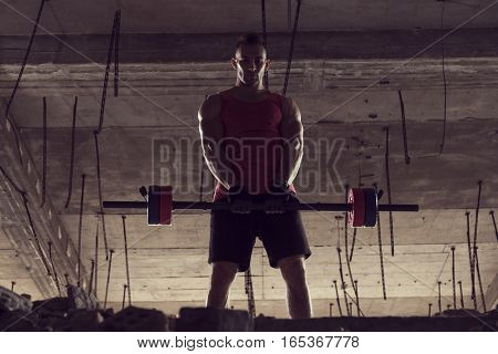 Young muscular man lifting a barbell in an abandoned building
