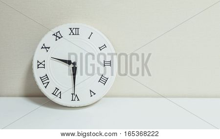 Closeup white clock for decorate show half past nine or 9:30 a.m. on white wood desk and cream wallpaper textured background with copy space