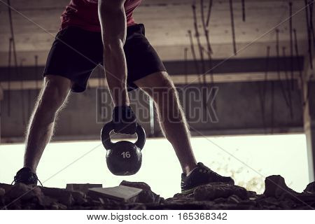 Detail of a young muscular athlete working out lifting a kettlebell weight in an abandoned ruined building