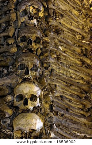 Photo of a wall in a chapel fully couvered with human bones.