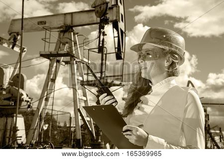 Woman engineer in yellow glasses on the oil field wearing red helmet and work clothes. Industrial site background. Toned sepia.