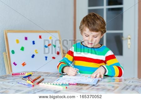 Portrait of cute happy school kid boy at home making homework. Little child writing with colorful pencils, indoors. Elementary school and education.