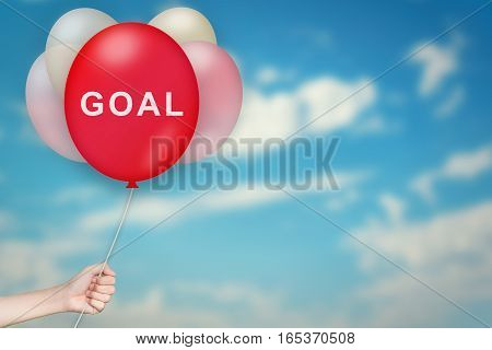 Hand Holding goal Balloon with sky blurred background