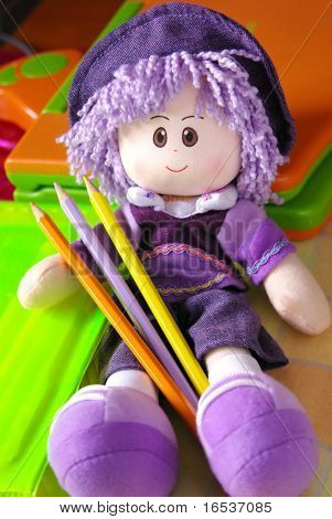Purple wool smiling doll with colorful pencils
