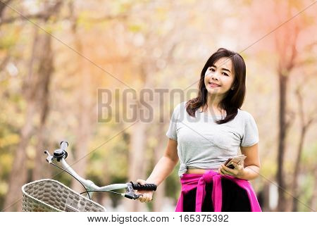 Attractive woman posing with phone and bicycle in countryside road lifestyle concept vintage tone