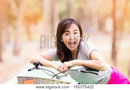 Attractive healthy mature woman ride bicycle and expression of surprise in countryside lifestyle concept vintage tone