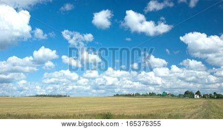 Countryside summer landscape with many clouds on blue sky and village at skyline