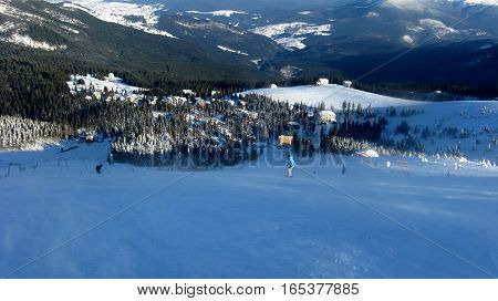 View from the high to the ski resort which attracts skiers on the ski slopes a village in winter mountains the snow-capped mountain peaks.