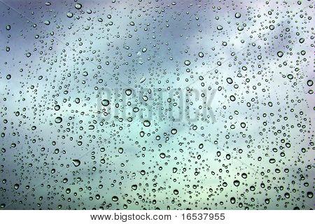 Ventana mojado con gotas de lluvia y un cielo tempestuoso nublado afuera