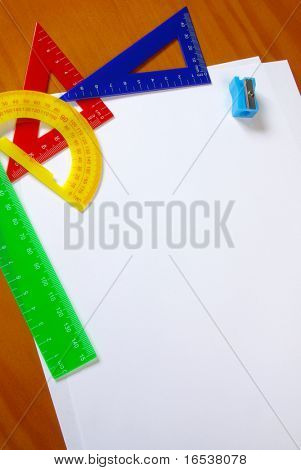 Colorful student gear and blank sheets of paper over wooden table