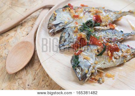 fried mackerel spicy Thai style food on wood dish