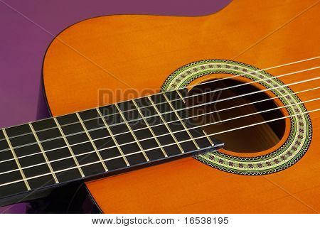 Closeup detail of a classic guitar over purple background