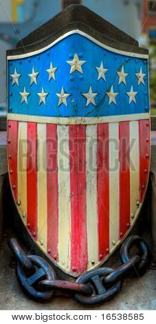 An HDR image of a metal american flag emblem at the base of a memorial