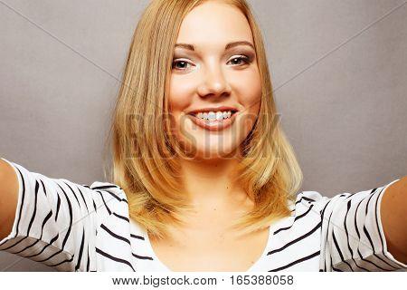 Selfie time. Joyful young women making selfie by her smart phone over grey background