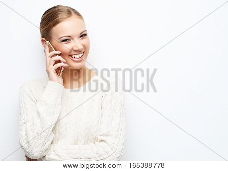 Pretty blond woman  talking on the mobile phone over white background