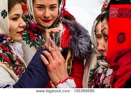Uzhgorod Ukraine - January 15 2017: Members of folklore groups use the mobile phone as a mirror during the seventh ethnic festival Christmas Carols in the old village. During the festival visitors can familiarize with a variety of Christmas customs caroli