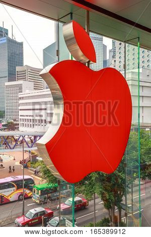Hong Kong, China - December 4, 2016: close up of Red Apple sign in Apple store, IFC Mall, with Central District skyline on background. Apple is world leader in consumer tablets, computers and mobiles.