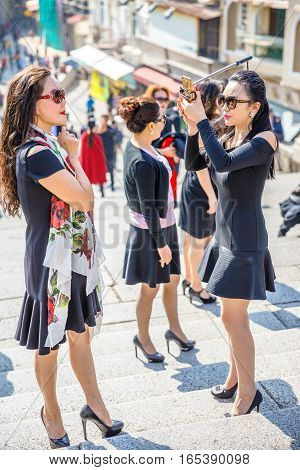 Macau, China - December 8, 2016: typical asian women with branded clothes and luxury accessories take a selfie on staircase of the Ruins of St. Paul's, historic Macau, a popular tourist destination.