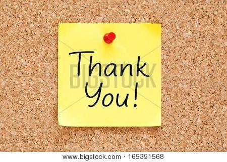 Thank You handwritten on yellow sticky note pinned on bulletin cork board.