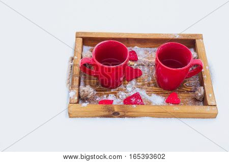 Two red cups with tea on a wooden tray in snow. Romantic Valentine's day winter picnic hot tea couple. Lifestyle time together outdoors Valentine's day. Snowflakes hoarfrost and heart shape on a tray. Copy space