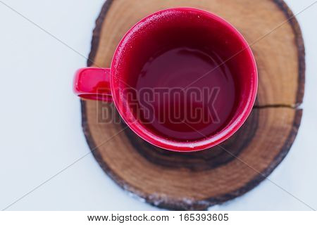 Red cup with tea on a wood slice in snow. Romantic winter picnic hot tea. Lifestyle time together outdoors. Copy space