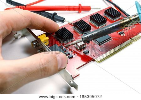 The installation of repair part on the DVR motherboard with a soldering iron on a white background