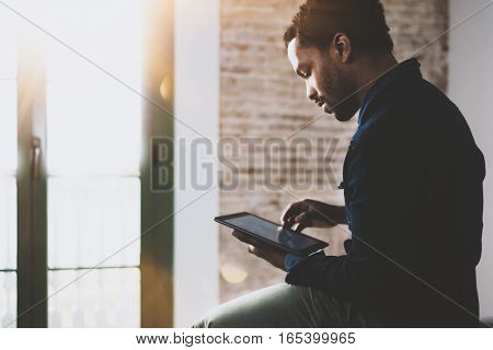 Pensive young African American freelancer touching screen digital tablet while working in new project at home. Black businessman looking for information on Internet. Blurred, color filter, flares.