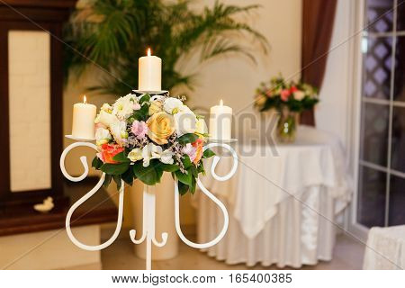 three burning candles and a bouquet. Decoration of the hall for the wedding ceremony